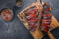 Barbecue chuck beef ribs with hot marinade and chili sauce as top on a wooden cutting board with copy space
