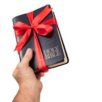 Hand giving the gift of the Holy Bible