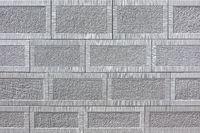 Detail einer Wand aus grauem viereckigen Sandstein mit Muster
