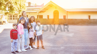 Gruppe Kinder in Grundschule mit Lehrer auf Schulhof