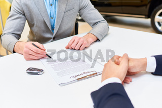 Man Signing Papers to Buy Car