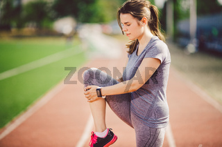 Beautiful young caucasian woman with long hair in tail and big breasts doing exercises, warming up and warming up muscles before training in running stadium, red rubber track in summer on a sunny day