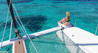 Woman relaxing on a summer sailing cruise, sitting on a luxury catamaran in picture perfect turquoise blue lagoon near Spargi island in Maddalena Archipelago, Sardinia, Italy.