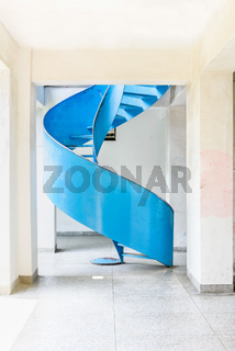 Blue abstract metal spiral ladder in bright room