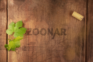 A design template for a wine menu or tasting invitation. A vine leaf and a wine cork, shot from above on a dark rustic wooden background with copy space