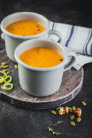 Pumpkin soup in a metal mugs on wooden board