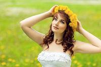 beautiful girl with dandelion flowers in green field