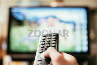 Male hand is holding TV remote control, streaming on a smart TV.