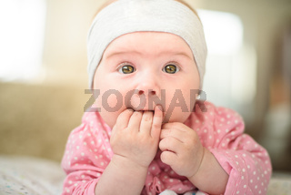 Cute 6 months old Baby girl infant on a bed on her belly with head up and fingers in mouth, looking towards camera with her big eyes.