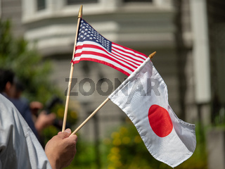 Japan and United States (USA) flag being waved by a hand