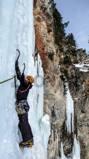 male ice climber on a steep frozen waterfall on a beautiful winter day in the Swiss Alps