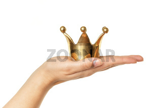 Female hand holding golden crown isolated on white background
