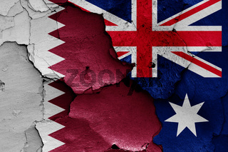 flags of Qatar and Australia painted on cracked wall