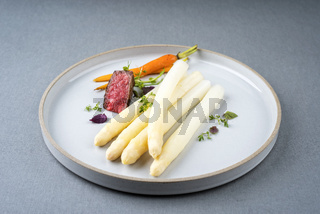 Modern barbecue dry aged sliced fillet steak with white asparagus and roast carrot as closeup on a plate with copy space