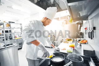 happy male chef cooking food at restaurant kitchen