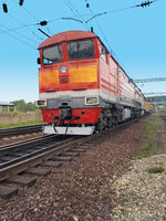 red diesel locomotive on the tracks in motion
