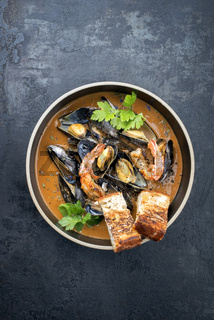 Traditional French Corsican seafood stew with prawns and mussels as top view in a modern design bowl with copy space