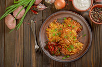 Top view at flat lay potato pancakes in clay dish with sun-dried tomatoes and sour cream