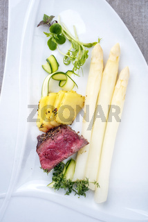 Modern barbecue dry aged sliced fillet steak with white asparagus and roast potatoes as top view on a plate