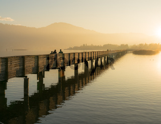 long wooden boardwalk pier over water in golden evening light with a mountain landscape and people w