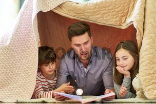 Vater liest seinen Kindern aus einem Buch vor