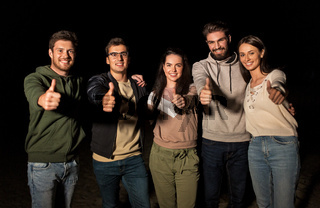 happy smiling friends showing thumbs up at night