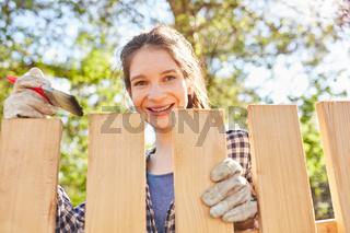 Lächelnde junge Frau beim Zaun streichen