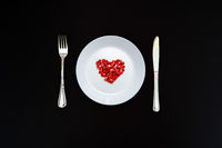 On a white plate from pomegranate seeds composite heart shape. Knife and fork next to the plate. Black background. Flat layer.