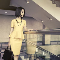 Young fashion business woman in yellow peplum dress with handbag at office