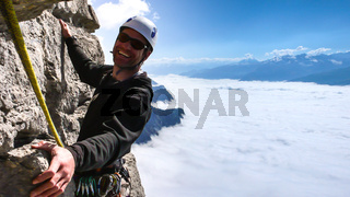 male mountain guide smiling on a steep vertical rock climb above the clouds
