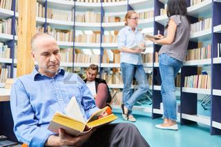 Mann als Dozent beim Buch lesen im Lesesaal