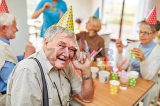 Alter Mann mit Partyhut feiert Geburtstag