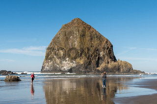 An adult couple take a photo with the phone to a young couple with Haystack Rock in the background at Cannon beach