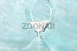 Time is running out concept. A close-up of an hourglass with sand falling through, on a teal blue background with a place for text