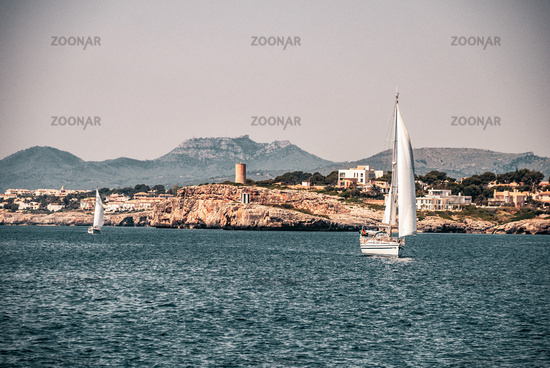 Two sail ships with porto cristo in background