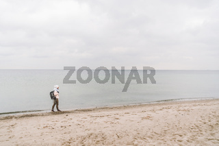 One caucasian man young caucasian woman tourist with a black backpack on a sandy beach near the Baltic sea in winter. Theme trip alone. Thoughts and dreams overlooking the horizon