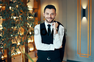 Happy handsome man in elegant suit in modern luxury interior