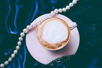Cup of cappuccino for breakfast with satin and pearls jewellery background, organic coffee with lactose free milk in parisian cafe for luxury vintage holiday brand