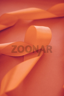 Abstract curly silk ribbon on orange background, exclusive luxury brand design for holiday sale product promotion and glamour art invitation card backdrop