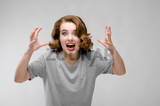 Charming young girl in a gray T-shirt on a gray background. The girl screams