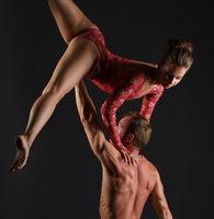 Duet of acrobats perform trick in studio