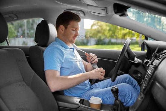 man or car driver fastening seat belt