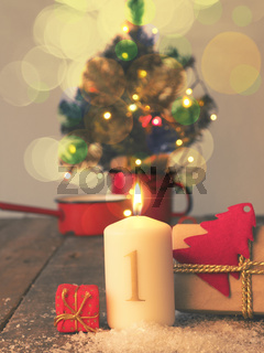 First Advent candle burning with gift boxes, vintage tone stylized