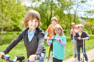Kinder machen Ausflug mit Roller und Fahrrad