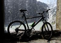 Mountainbike unter einem Wasserfall, Val de Bagnes, Wallis, Schweiz