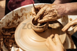 Expert potter teach a child to work on potter wheel