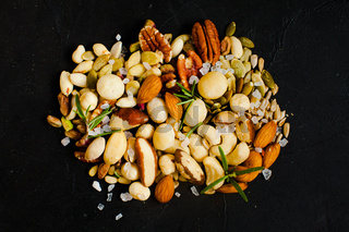 Healthy snack, assortment of different nuts on a black background