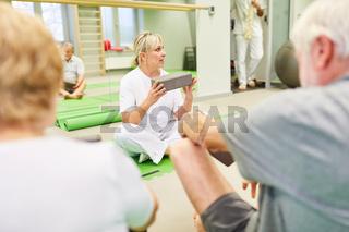 Trainer mit Yogablock erklärt Senioren Rückenübung