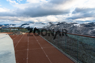 Mountains landscape, Geirangerfjord and winding road Nibbevegen from Dalsnibba viewpoint, Geiranger Skywalk platform floor surface, Norway.
