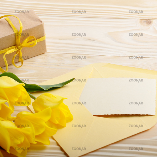 Yellow tulips near blank greeting card gift box and envelope on natural wooden background with space for text